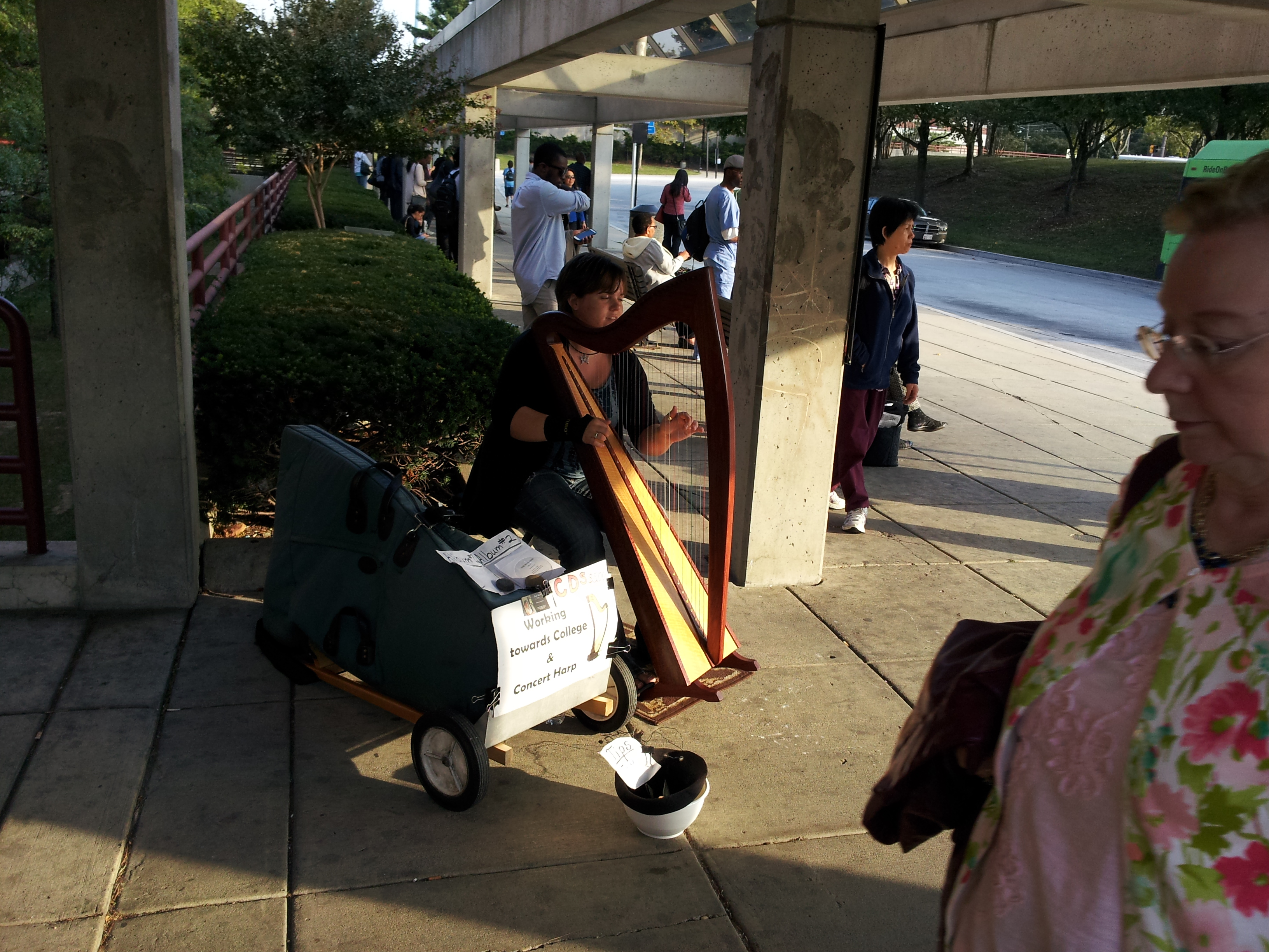 A harpist playing outside of a Metro station.